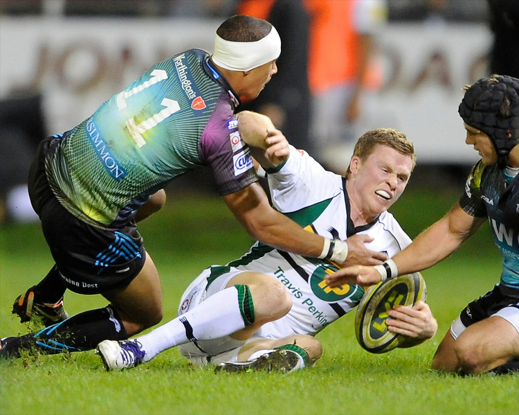 Chris Ashton of Northampton Saints (centre) is tackled by Eli Walker (left) and Matthew Morgan of Ospreys during the LV= Cup second round match between Ospreys and Northampton Saints at Riverside Hardware Brewery Field, Bridgend (Photo by Rob Munro)