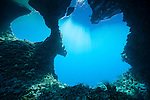 Misool, Raja Ampat, Indonesia; sunlight streams through the water on the other side of Boo Windows
