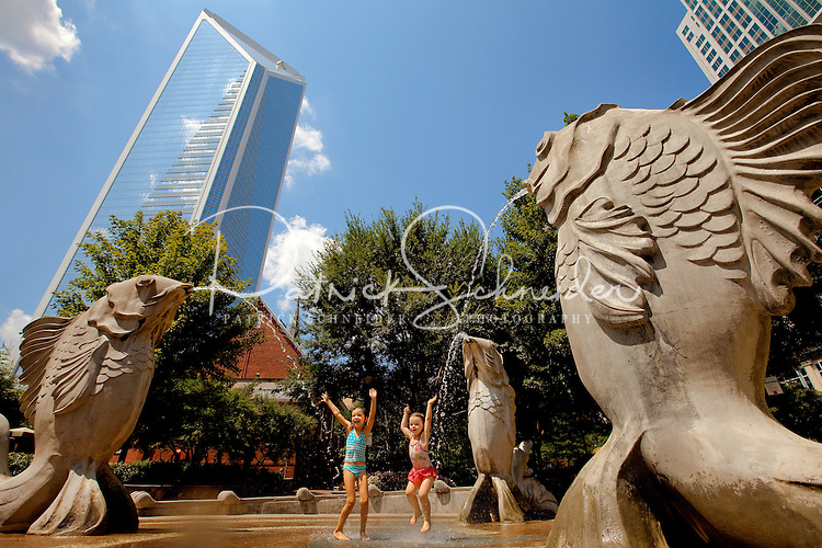 Young girls play on the Fish Fountain, one of many public art pieces in The Green in downtown Charlotte. The Green, located at 435 South Tryon St., is a popular urban park in the heart of Charlotte, NC.