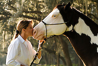 Middle age American Indian woman kisses her American Paint Horse stallion on nose.