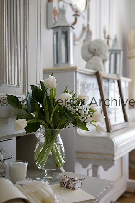A vase of white tulips on a drop-leaf desk beside the piano in the living room