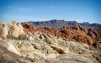 Valley of Fire State Park is located only six miles from Lake Mead and 55 miles northeast of Las Vegas. Valley of Fire is Nevada's oldest and largest state park. The Valley of Fire derives its name from red sandstone formations, and the stark beauty of the Mojave Desert. formed from great shifting sand dunes during the age of dinosaurs, 150 million years ago. Complex uplifting and faulting of the region, followed by extensive erosion, have created the present landscape. Other important rock formations include limestones, shales, and conglomerates. Ancient trees and early man are represented throughout the park by areas of petrified wood and 3,000 year-old Indian petroglyph. Popular activities include camping, hiking, picnicking and photography.