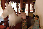 A devotee works her hands over a white marble horse at the Shwezigon Pagoda.   Pagoda Bagan. Myanmar (Burma.) 2006