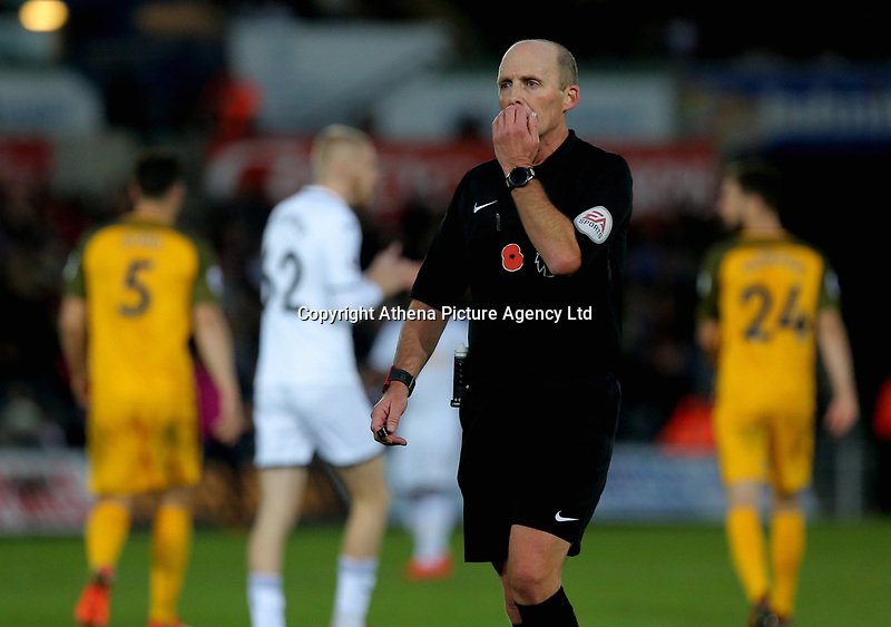 Referee Mike Dean covers his mouth as he speaks to Mathew Ryan of Brighton during the Premier League match between Swansea City and Brighton and Hove Albion at The Liberty Stadium, Swansea, Wales, UK. Saturday 04 November 2017