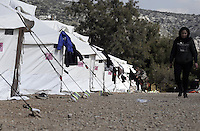 Pictured: A refugee woman walks by a row of tents Friday 26 February 2016<br /> Re: Hundreds of refugees have been given temporary shelter at the Stefanakis Army Camp in the Schisto area of Athens, Greece.