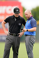 General manager Eric Jarinko of the Greenville Drive discusses the weather with umpire Adam Pierce during a game against the Asheville Tourists on Tuesday, August 31, 2021, at Fluor Field at the West End in Greenville, South Carolina. (Tom Priddy/Four Seam Images)