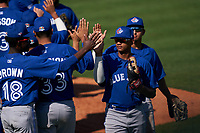 Toronto Blue Jays Yhoangel Aponte (44) high fives teammates, including Dasan Brown (18), after a Minor League Spring Training game against the Detroit Tigers on April 22, 2021 at Tigertown in Lakeland, Florida.  (Mike Janes/Four Seam Images)