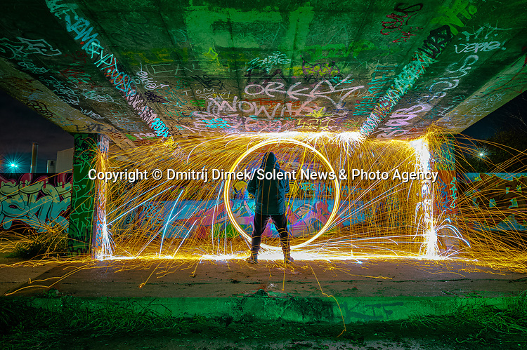 """Pictured:  Grays, West Thurrock, London.<br /> <br /> Amazing photos show sparks illuminating British landmarks as they fly from what appears to be a disc of colourful light.  This unique effect is the result of long-exposure night-time shots of a whisk stuffed with steel wool, which is set alight and spun at the end of a metal chain.<br /> <br /> Amateur photographer Dmitrij Dimek is passionate about what he calls 'light paintings', and took these photos at castles, beaches and other settings around Essex and London.  The 38 year old, who grew up in Poland but now lives in Southend-on-Sea, Essex, said: """"When I first found out about light painting with steel wool, I thought it was an outstanding way to connect with photography.  SEE OUR COPY FOR DETAILS.<br /> <br /> Please byline: Dmitrij Dimek/Solent News<br /> <br /> © Dmitrij Dimek/Solent News & Photo Agency<br /> UK +44 (0) 2380 458800"""