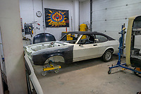 BNPS.co.uk (01202) 558833. <br /> Pic: MattRichardson/Classic Ford/BNPS<br /> <br /> Pictured: The restoration in process. <br /> <br /> The legendary Ford Capri that starred in '80s TV show Minder has been restored to its former glory after a devastating fire wrecked the car.<br /> <br /> The 1977 white motor which appeared on the opening titles of the comedy-drama caught ablaze while it was returning from an MoT test last year.<br /> <br /> It is thought an electrical fault in the engine bay caused the fire. <br /> <br /> Now a mechanic who specialises in classic car restorations has unveiled the famous Ford after fixing it up over the past six months.