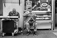 A blind man, accompanied by his fellow musician, earns money by singing on the street of Santiago de Chile, Chile, 20 March 2002.
