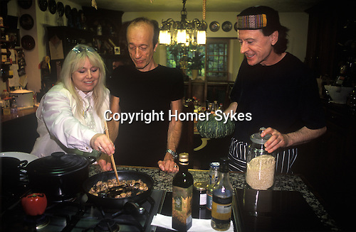 Dwina Gibb and Robin Gibb of the pop group Bee Gees 2000s at their home in the Home Counties UK. Seen here in the kitchen with their chef.
