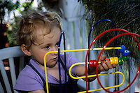 Two year girl playing with an abacus.