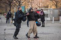 """Etwa 3 dutzend Menschen versuchten am Samstag den 28. Maerz 2020 in Berlin-Mitte, trotz einem allgemeinen Versammlungsverbot durch die Behoerden sich zu einer """"Hygienedemo"""" zu versammeln. Ihre Forderung war """"fuer unsere Verfassung, das Grundgesetz, sowie Transparenz, Pressefreiheit, Wahlen und vollstaendige Demokratie & Transparenz bei der Einsetzung neuer Wirtschaftsgesetze in Form einer """"Verfassung der Oekonomie"""".<br /> Es wurden Exemplare des Grundgesetz verteilt. Die Polizei forderte die Menschen auf sich zu zerstreuen und nach ca. 30 Minuten nahm sie von Menschen, die der Aufforderung nicht nachkamen die Personalien auf und erteilte Platzverweise.<br /> Aufgerufen zu der Aktion hatte eine Gruppe namens """"nichtohneuns.de"""".<br /> Im Bild: Polizeibeamte fuehren einen jungen Mann ab.<br /> 28.3.2020, Berlin<br /> Copyright: Christian-Ditsch.de<br /> [NUR FUER REDAKTIONELLE ZWECKE! Werbung nur auf Anfrage beim Fotografen. Inhaltsveraendernde Manipulation des Fotos nur nach ausdruecklicher Genehmigung des Fotografen. Vereinbarungen ueber Abtretung von Persoenlichkeitsrechten/Model Release der abgebildeten Person/Personen liegen nicht vor. NO MODEL RELEASE! Don't publish without copyright Christian-Ditsch.de, Veroeffentlichung nur mit Fotografennennung, sowie gegen Honorar, MwSt. und Beleg. Konto: I N G - D i B a, IBAN DE58500105175400192269, BIC INGDDEFFXXX, Kontakt: post@christian-ditsch.de<br /> Bei der Bearbeitung der Dateiinformationen darf die Urheberkennzeichnung in den EXIF- und  IPTC-Daten nicht entfernt werden, diese sind in digitalen Medien nach §95c UrhG rechtlich geschuetzt. Der Urhebervermerk wird gemaess §13 UrhG verlangt.]"""