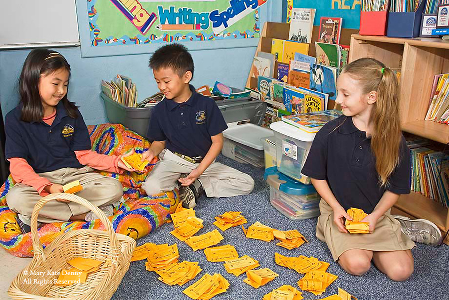 Two Vietnamese American children and one Caucasian girl_seven years old_in uniforms count play money in reading corner of elementary schoolroom in New Orleans