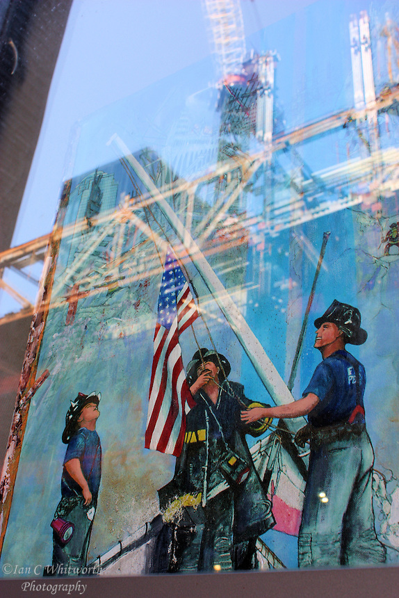 A view of a picture of the firefighters in the window at ground zero memorial with the new construction at the World Trade Center site caught in the reflection