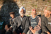 Shimla, Himachal Pradesh, India. Group of pensioners sitting on a bench, laughing.