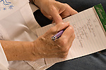 """closeup of hands of senior woman in late 70s writing """"to do"""" list on pad horizontal"""