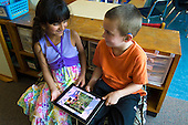 MR / Schenectady, NY. Zoller Elementary School (urban public school). Kindergarten inclusion classroom. Two students use iPad to read an educational eBook / app. Boy: 5, hearing impaired; Girl: 5, biracial  MR: Shu20, Myk1. ID: AM-gKw. © Ellen B. Senisi.