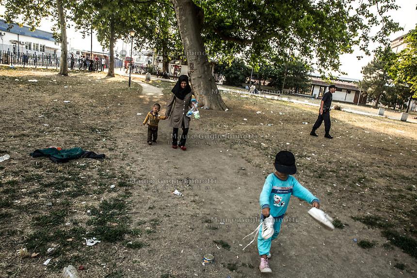 Migranti nel parco della stazione dei bus di Belgrado. Migrants on the bus station park in Belgrade Beograd<br /> Un bambino con due scarpe in mano seguito da madre e fratellino. sullo sfondo un poliziotto . A child with two shoes in hand , followed by mother and brother . in the background a cop