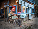 Brusko Antonic, owner of the International Cafe and resident Serbian, Austin, Nevada, sit barefoot in front of his bar in the middle of the state along US 50, Loneliest Highway in America