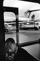 Switzerland. Zürich Airport. Planes at gates. Swissair flight on the tarmac. A black man sits in a transit bus.  Swissair was the former national airline of Switzerland. For most of its 71 years, Swissair was one of the major international airlines and was regarded as a Swiss national symbol and icon. The airline was declared bankrupt on March 31 2002. © 1995 Didier Ruef