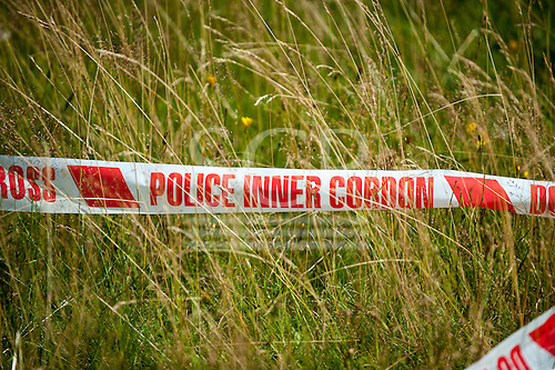 Rural England. Red and white Police tape in a field.