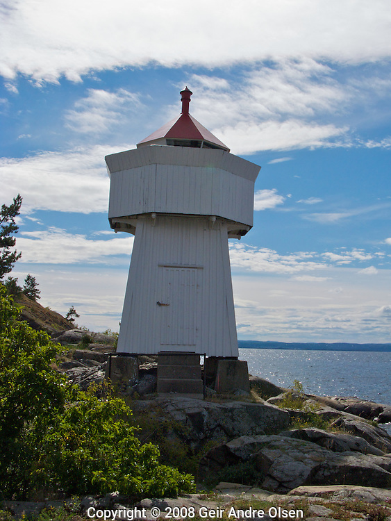 View of a small, white lighthouse with a red roof at Ramvikholmen outside Tofte at the Hurum peninsula, Norway on a beautiful summer day.