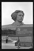 A woman offers flowers in front of the statue of a young Chairman Mao Zedong at the central city of Changsha, Hunan Province, China, October 2019. The enormous statue stands more than 100ft tall.