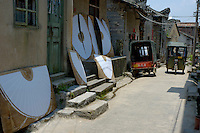 Umbrella parts leaning against the facade of a factory to dry in the sun, Fuli Village, Guangxi, China.