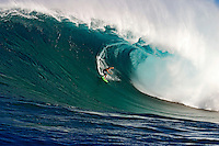 A tow-in surfer drops below the curl of Hawaii's big surf at Peahi (Jaws) off Maui.<br />