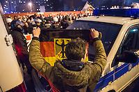 """Etwa 200 Anhaenger des Berliner Ablegers rechten Pegida-Bewegung, Baergida, versammelten sich am Montag den 5. Januar 2015 in Berlin zu einer Demonstration gegen eine angebliche Islamisierung Deutschlands und dagegen, dass """"in 30 Jahren in Deutschland die Sharia herrscht"""", so der Organisator Karl Schmitt.Bis zu 5.000 Menschen protestierten gegen den rechten Ausmarsch und blockierten bei Regen die Marschroute mehrere Stunden. Die Polizei schaffte es nicht mit koerperlicher Gewalt die Blockade zu beenden, so dass die Rechten nach drei Stunden nach Hause gehen mussten. Die Baergida-Anhaenger, """"Berlin gegen die Islamisierung des Abendlandes"""", feierten dies aber dennoch als Sieg. Waren zur ersten Baergida-Aktion eine Woche zuvor nur 5 Menschen gekommen.<br /> Unter den Anhaengern von Baergida waren viele bekannte militante Neonazis und Hooligans sowie Mitglieder der Rechtsparteien AfD und Pro Deutschland und der rechtsradikalen German Defense League. Immer wieder wurde skandiert """"Luegenpresse, auf die Fresse"""" und dass die Journalisten nach Israel verschwinden sollen.<br /> Im Bild: Ein Rechter schwenkt seine Deutschlandfahne in Richtung der Gegendemonstranten.<br /> 5.1.2015, Berlin<br /> Copyright: Christian-Ditsch.de<br /> [Inhaltsveraendernde Manipulation des Fotos nur nach ausdruecklicher Genehmigung des Fotografen. Vereinbarungen ueber Abtretung von Persoenlichkeitsrechten/Model Release der abgebildeten Person/Personen liegen nicht vor. NO MODEL RELEASE! Nur fuer Redaktionelle Zwecke. Don't publish without copyright Christian-Ditsch.de, Veroeffentlichung nur mit Fotografennennung, sowie gegen Honorar, MwSt. und Beleg. Konto: I N G - D i B a, IBAN DE58500105175400192269, BIC INGDDEFFXXX, Kontakt: post@christian-ditsch.de<br /> Bei der Bearbeitung der Dateiinformationen darf die Urheberkennzeichnung in den EXIF- und  IPTC-Daten nicht entfernt werden, diese sind in digitalen Medien nach §95c UrhG rechtlich geschuetzt. Der Urhebervermerk wird gemaess §13 UrhG verlangt.]"""
