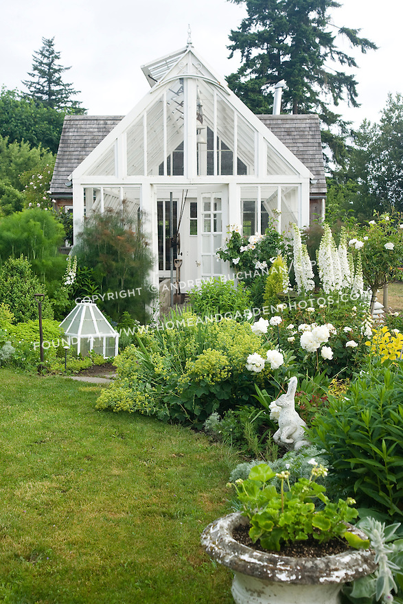 This white-painted greenhouse was salvaged from a local arboretum and restored for use here, and adds to the romantic, cottage garden feel of the Sissinghurst-style white garden behind the late 19th c. farmhouse on this property.  The garden includes white peonies, delphiniums, and foxglove, white climbing and shrub roses, and garden flox, among others. Garden design by Toni Christianson, Christianson's Nursery
