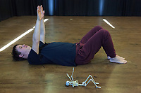 Switzerland. Canton Ticino. Locarno. Fauni Theater.  MOPS_DanceSyndrome is an independent Swiss artistic, cultural and social organisation operating in the field of contemporary dance and disability. It is composed only of Down dancers. Vinzenz Häussermann is laying on his back on the floor. He is moving his arms and legs. He is making the same move as the human plastic skeleton. Down syndrome (DS or DNS), also known as trisomy 21, is a genetic disorder caused by the presence of all or part of a third copy of chromosome 21 It is usually associated with physical growth delays, mild to moderate intellectual disability, and characteristic facial features. 19.12.2019 © 2019 Didier Ruef