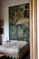 An alcove bed is a curious fantasy of four peacock posts set off by an eighteenth century tapestry depiciting an exotic forest in tones of blue.