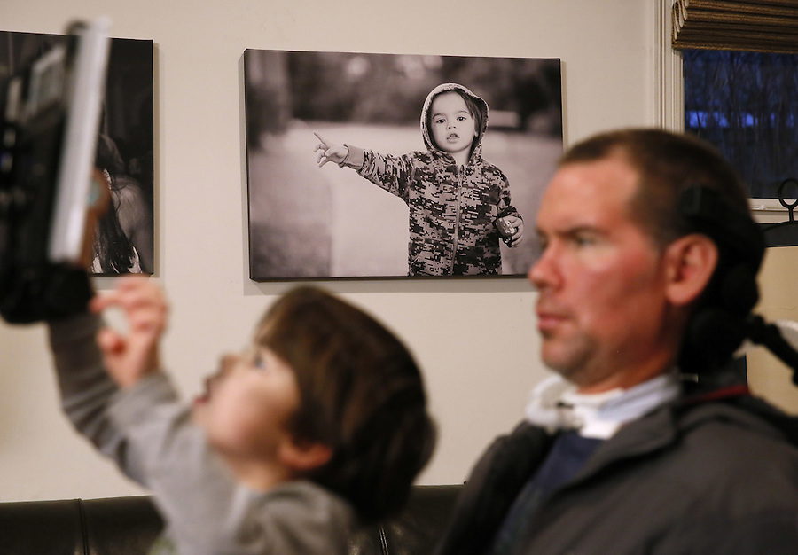 """In this Monday, Jan. 18, 2016 photo, former New Orleans Saints NFL football player Steve Gleason watches as his four-year-old son, Rivers, plays on his father's tablet during an interview in New Orleans. """"GLEASON,"""" a feature-length documentary that gives an unfiltered look at his life with ALS premieres at the Sundance Film Festival on Saturday. (AP Photo/Jonathan Bachman)"""