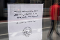 A sign on the front door of Democracy Brewing in Downtown Crossing indicates that the establishment is temporarily closed in hibernation until Spring/Summer 2021 due to restrictions on restaurants put in place during the ongoing Coronavirus (COVID-19) global pandemic in Boston, Massachusetts, on Sat., Jan. 9, 2021.