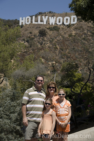 A family poses in front of the Hollywood Sign, Hollywood, Los Angeles, CA