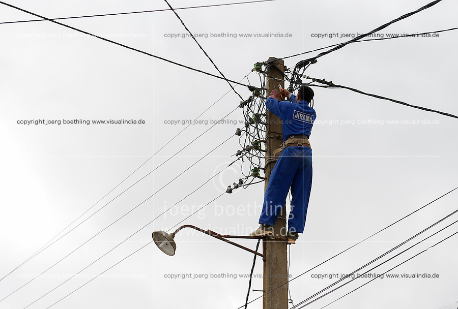 MADAGASCAR Antananarivo, Jirama ( Jiro sy rano malagasy) is a state-owned electric utility and water services company, worker repair electricity pylon  / MADAGASKAR Antananarivo, Jirama, der staatliche Stromnetzbetreiber, Arbeiter im Strommast
