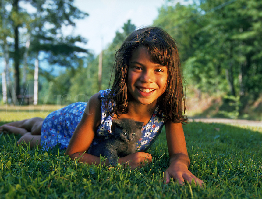 Hispanic girl smiling and lying in grass with her kitten.