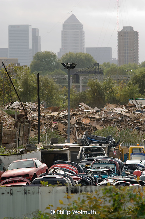 A vehicle scrapyard and builders' waste on derelict land in the Lower Lea Valley, site of the 2012 Olympic Games, close to Docklands and the Canary Wharf tower.