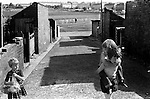 """South Kirkby Colliery Yorkshire England. 1979.  Children playing in back alley.<br /> <br /> The houses in the foreground of the picture are probably Wesley Street or Burton Street and are still there but the old outbuidings have gone now. In the far background the Council built """"White City Estate"""" in nearby South Elmsall going up towards Frickley Colliery"""