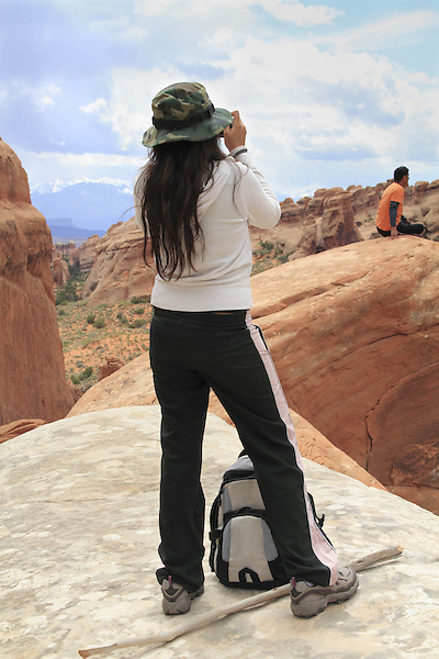 Young woman taking pictures of her boyfriend in Arches National Park, Utah, USA. .  John offers private photo tours in Arches National Park and throughout Utah and Colorado. Year-round.