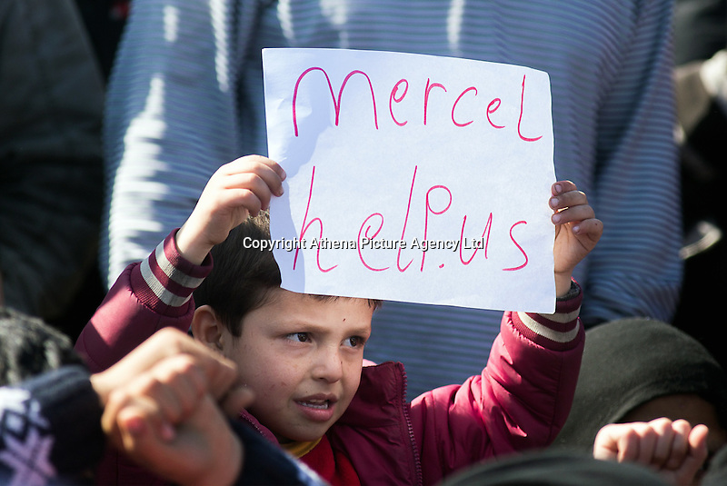 "Pictured: A little boy with a ""Merkel help us"" slogan on a piece of paper Thursday 03 March 2016<br /> Re: Migrants have closed off the railway track at the Greek Fyro Macedonian border in Idomeni, Greece,"