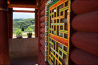 Brightly painted Tibetan log house with an open window and view.