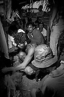 Contemporary slavery in Brazil, sugar and ethanol plant in Bahia State. Sugarcane cutters in the lodging at dawn trying to improvise a stove. No potable water , no electrical light, no hygiene and no kitchen facilities.