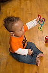 5 month old baby boy sitting shaking plastic toy chain