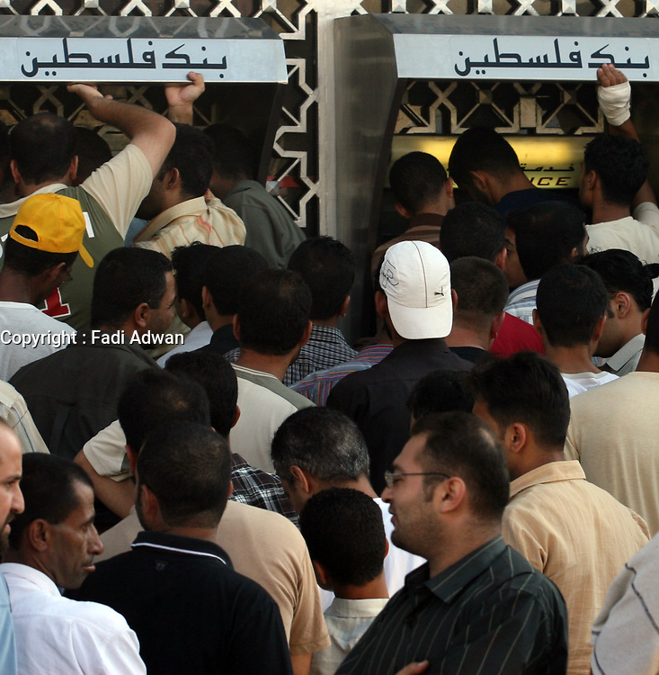 """Palestinian security force officers loyal to the Fatah movement wait in line at a bank machine to receive their salaries from Palestinian Authority Prime Minister Salam Fayyad's government in Gaza City, Tuesday, Aug. 7, 2007. It was the second payment of salaries by the government in Ramallah to officers in the Gaza Strip since Hamas took control in June. """"photo  by Fadi Fadi"""""""