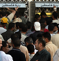 "Palestinian security force officers loyal to the Fatah movement wait in line at a bank machine to receive their salaries from Palestinian Authority Prime Minister Salam Fayyad's government in Gaza City, Tuesday, Aug. 7, 2007. It was the second payment of salaries by the government in Ramallah to officers in the Gaza Strip since Hamas took control in June. ""photo  by Fadi Fadi"""