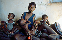 Angola. Cuando Cubango. Mavinga. Mother breastfeeding her twin sisters, both malnourished children,. She is seated on a bed in a hospital run by MSF (Médecins Sans Frontières) Switzerland. The twin brothers are also her children, they sit each on her side. One of her daughter will die a few days later. © 2002 Didier Ruef