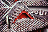 A fine art travel detail of Beijing roof tile patterns, showing an inverted, curved red arch under a greyish arching roof structure of tiles, with tiles from the next structure in the background.